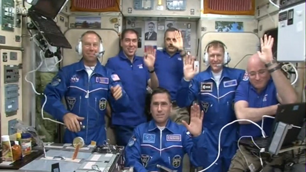 The crew wave goodbye after taking questions from Earth